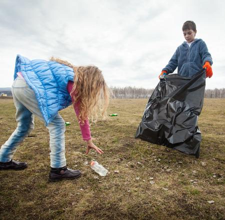 Kinder Reinigung Aufräumen. Kinder sammeln Müllsack im Wald