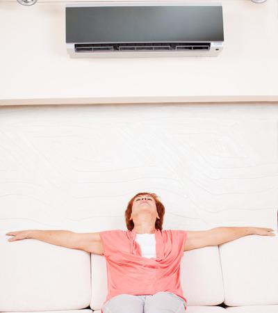 aire acondicionado: Mujer escapa del calor en el aire acondicionado en casa. Mujer madura feliz en el sofá