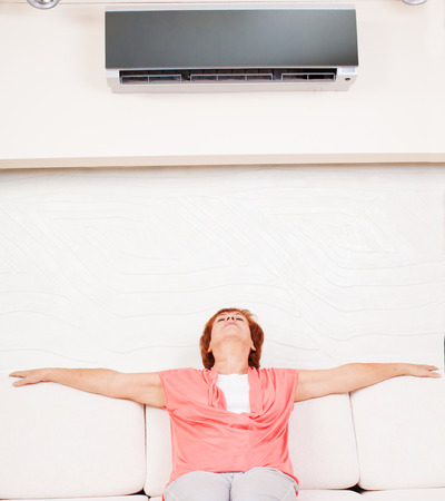 Woman escapes from the heat under the air conditioner at home. Happy mature woman on sofa