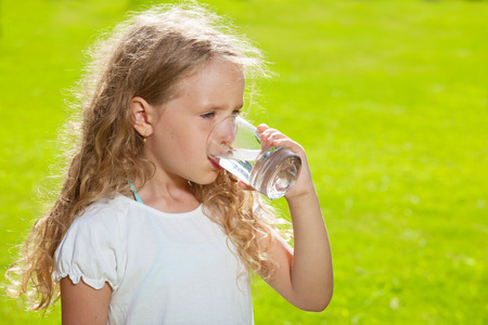 girl drinking water: Child drinking water. Girl outdoors Stock Photo