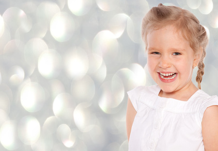 toothe: Little girl at gray background. Happy child
