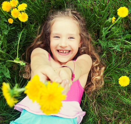 Child at summer. Happy girl outdoors on green grass Stock Photo - 28387861