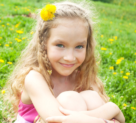 Child at summer. Happy girl outdoors on green grass photo