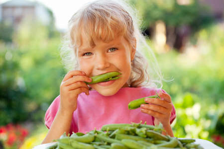 eating in the garden: Child eating pea pod outdoors