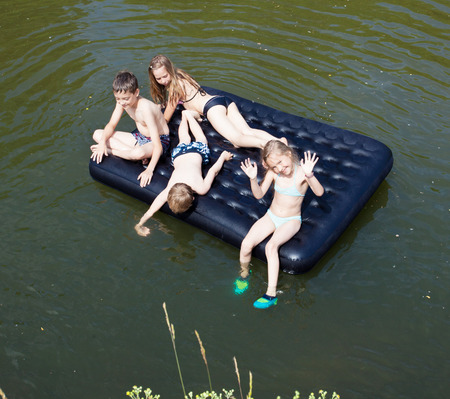 Children floating on the river on an inflatable mattress. Kids, summer, adventure photo