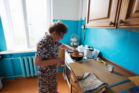 80 plus years: Elderly woman on the kitchen. Old woman at home Stock Photo