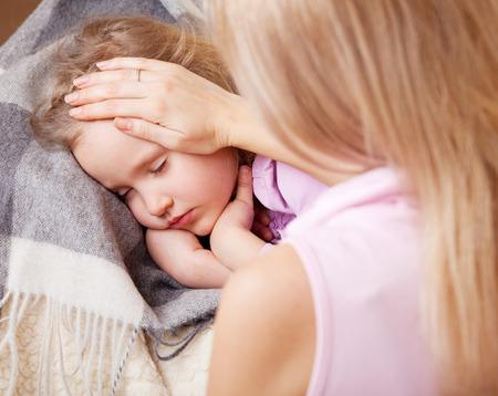 Parent touching forehead child. Illness child