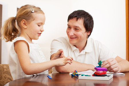 Family molded from clay toys. Father play with girl photo