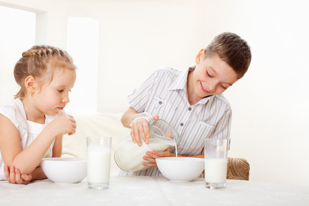 niños desayunando: Los niños comen desayuno. Familia comiendo cereales con leche