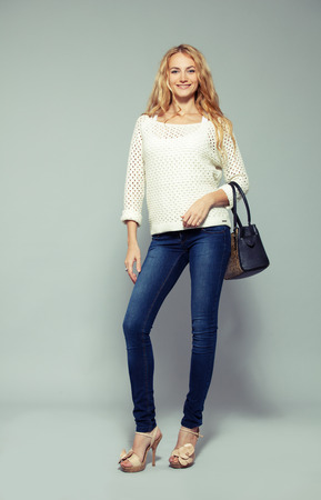 girls in jeans: Happy woman with handbag in studio