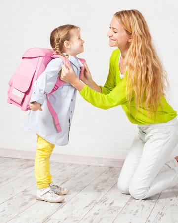 niño con mochila: Madre ayuda a su hija a prepararse para la escuela. Apoyo Mamá hijo use una mochila
