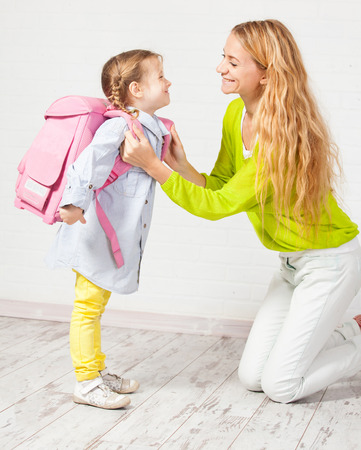 Mutter hilft ihrer Tochter für die Schule fertig. Mom Unterstützung Kind einen Rucksack tragen Standard-Bild