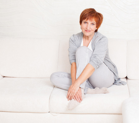mature women only: Happy mature female on sofa. Smiling middle woman at home