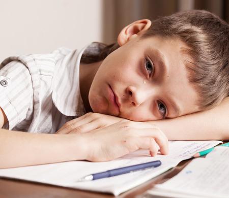niños escribiendo: Muchacho triste hacer la tarea. Niño llorando.