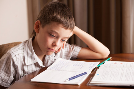 deberes: Muchacho triste hacer la tarea. La educación infantil
