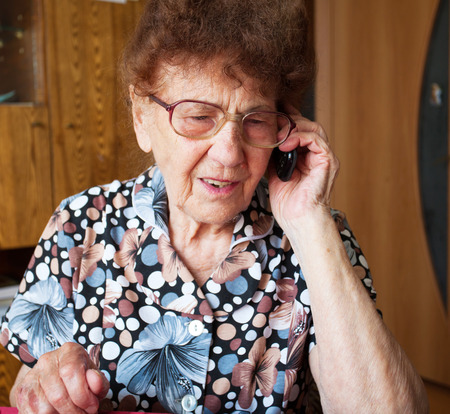 Old woman. Elderly female at home talking for mobile phone photo
