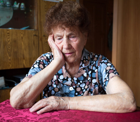 Old woman. Elderly sad female at home