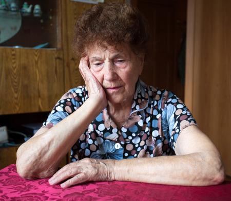 Oude vrouw. Ouderen trieste vrouw thuis