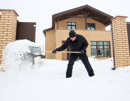 Man cleans snow shoveling around the house.  photo
