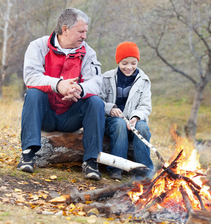 campfires: Grandfather and grandson around a campfire in the woods Stock Photo