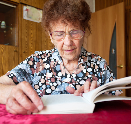 80 plus years: Elderly female at home reading Book Stock Photo