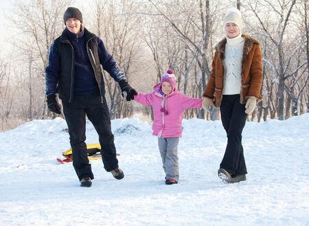 niños caminando: Familia caminando en un parque de invierno. Los padres con el niño en trineo