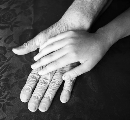 Two hands. Old and young. Childs hand on arm of an mature woman photo