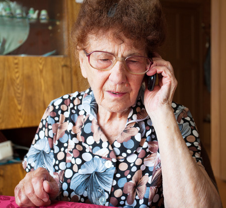 Old woman talking on mobile phone. Elderly, mature female at home photo