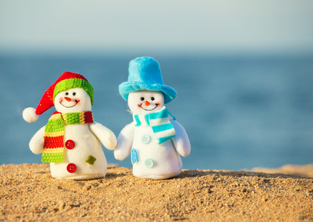 christmas scenic: Two snowmans on sand near sea. Christmas decoration. Vacations