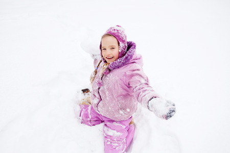 snowballs: Child in winter. Happy girl playing snowballs