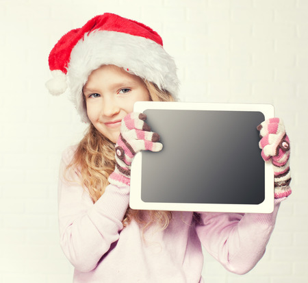 Child in christmas hat with tablet. Girl with pc photo