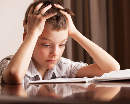 Boy doing homework. Sad child Stock Photo