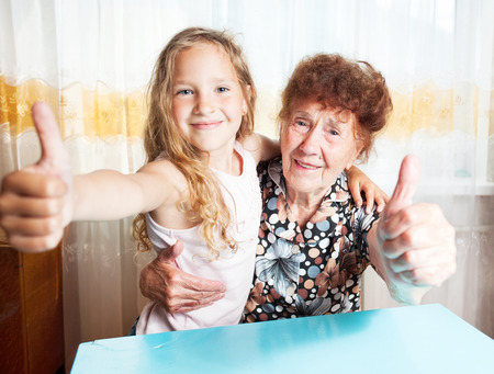 80 plus adult: Senior with girl. Generation. Elderly woman with great-grandchild showing sign ok