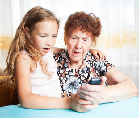 80 plus adult: Senior with girl. Generation. Elderly woman with great-grandchild looking at mobile phone