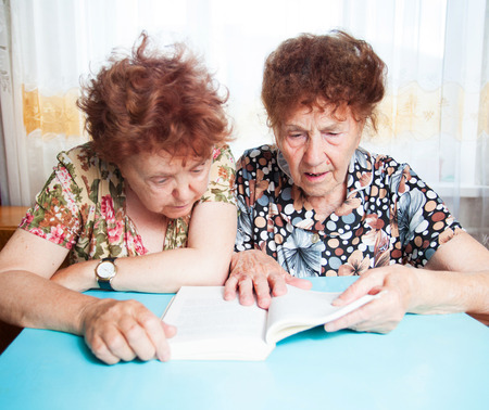 80 plus years: Two seniors. Old woman reading book. Friendship elderly