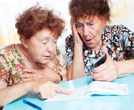 planificación familiar: Dos ancianas consideran recibos. Sorprendido Mujer cuenta con proyecto de ley Foto de archivo