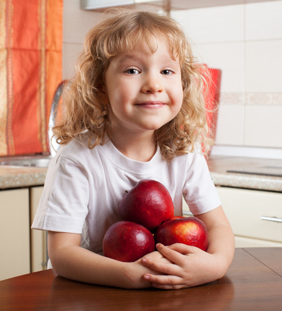 eating fruits: Ni�o que come frutas. Muchacha en la cocina con la manzana