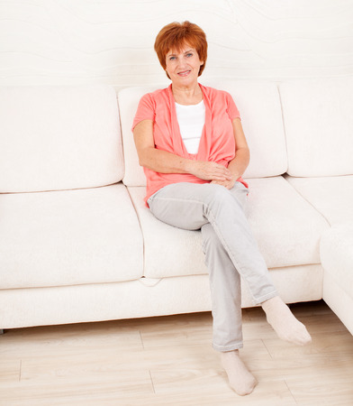 mature women only: Woman on sofa at home. Adult female