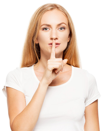 Woman at white background. Young female with his finger to lips attached photo