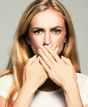 Woman with closed mouth. Female covers her mouth with her hands. Silence, fear, violence. Stock Photo