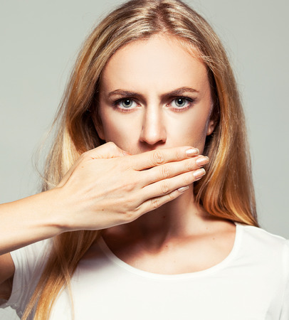 crooked: Woman with closed mouth. Female covers her mouth with her hands. Silence, fear, violence. Stock Photo