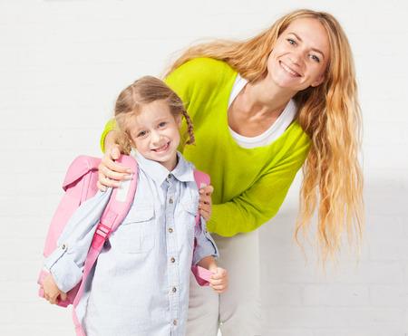 Moeder helpt haar dochter te krijgen klaar voor school. Mam ondersteuning kind om een rugzak te dragen
