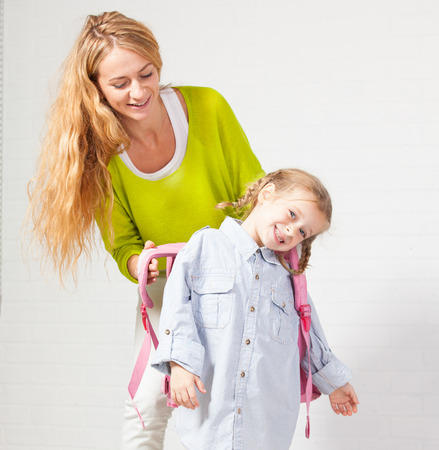 one child: Mother helps her daughter get ready for school. Mom support child to wear a backpack