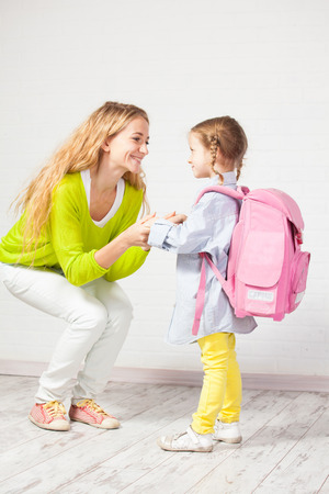 helps: Mother helps her daughter get ready for school. Mom support child to wear a backpack