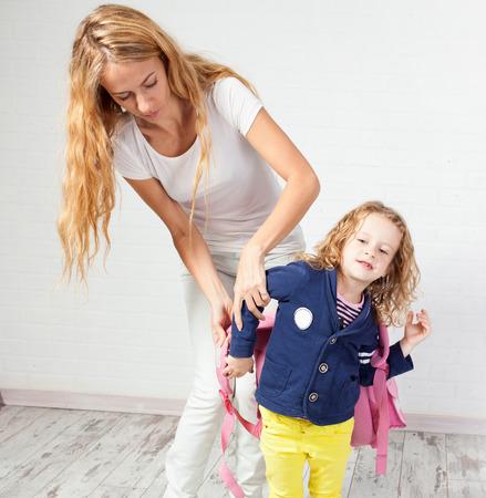 mochila escolar: Madre ayuda a su hija a prepararse para la escuela. Apoyo Mamá hijo use una mochila