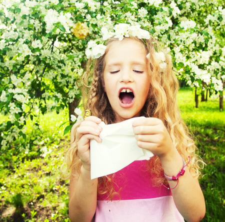 Sneezing girl. Child with a handkerchief. Allergy photo