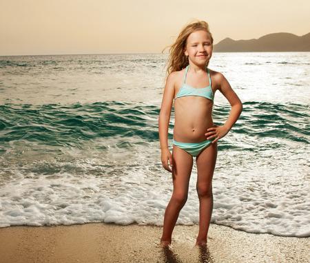 petite fille maillot de bain: Vacances. Fille sur la plage. Coucher de soleil.