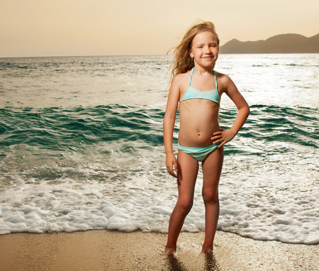 little girl beach: Vacations. Girl on the beach. Sunset. Stock Photo