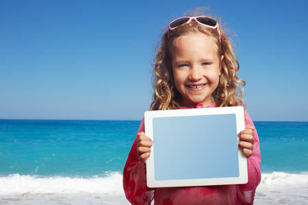 little girl beach: Child on the beach with tablet computer. Little happy girl showing screen digital pc