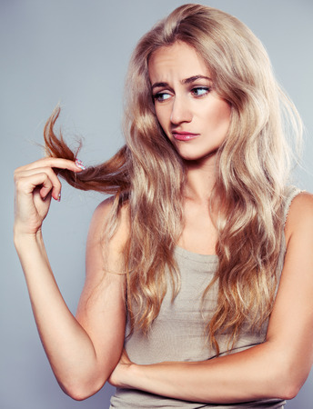 split: Young woman looking at split ends. Damaged long hair